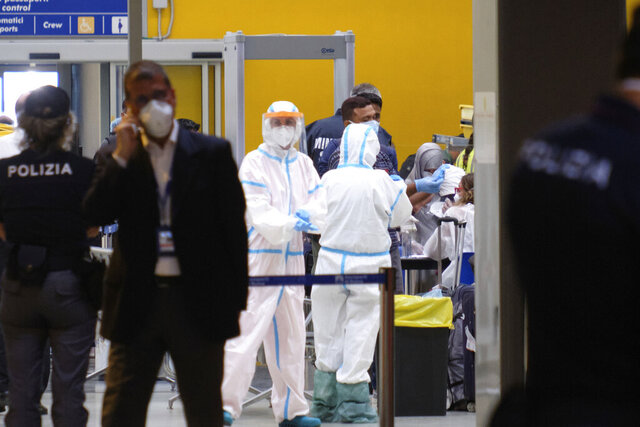 Italian Healthy ministry personnel check passengers who disembarked from a flight from Bangladesh at Rome's Leonardo Da Vinci international airport in Fiumicino, Monday, July 6, 2020. On Tuesday, July 7, 2020 Italy ordered a one-week suspension of incoming flights from Bangladesh after a spate of coronavirus cases near Rome were traced to members of the Bangladeshi community who had recently returned to Italy. Health Minister Roberto Speranza said in a statement Tuesday that beyond the dozen or so cases registered in recent days, more positive cases were traced to passengers on the latest flight that arrived in Rome on Monday. (Mauro Scrobogna/LaPresse via AP)