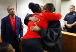 State District Judge Tammy Kemp, right, gives Botham Jean's mother, Allison Jean, a hug while Botham's father, Bertrum Jean, stands at left, following the 10-year sentence given to former Dallas Police Officer Amber Guyger for murder, Wednesday, Oct. 2, 2019, in Dallas. Guyger, who said she mistook neighbor Botham Jean's apartment for her own and fatally shot him in his living room, was sentenced to a decade in prison. (Tom Fox/The Dallas Morning News via AP, Pool)