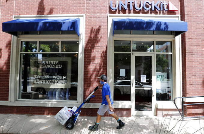 A delivery driver pushes a cart past an Untuckit men's clothes store in Dallas, Tuesday, July 7, 2020. Some big corporate names are on the government's list of 650,000 recipients of coronavirus relief loans despite the controversy that prompted other high-profile businesses to return billions of dollars in loan. Untuckit, which has 85 shirt stores, received a loan between $5 million and $10 million; the company said it used the money to keep paying its workers. (AP Photo/LM Otero)