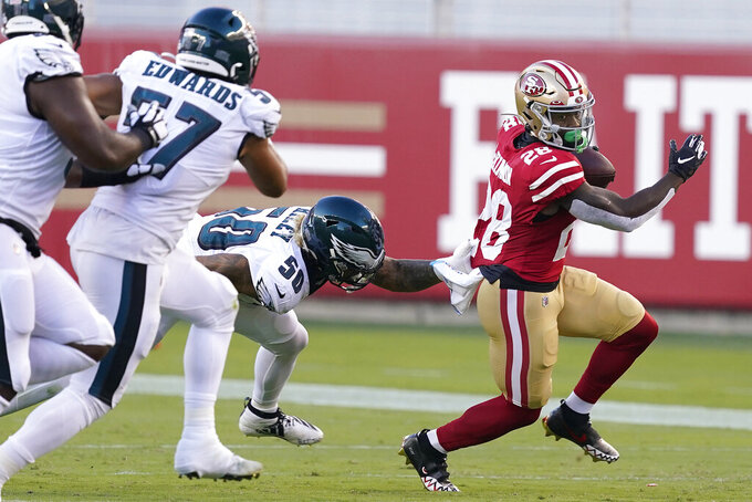 San Francisco 49ers running back Jerick McKinnon (28) runs against Philadelphia Eagles middle linebacker Duke Riley (50) and linebacker T.J. Edwards (57) during the first half of an NFL football game in Santa Clara, Calif., Sunday, Oct. 4, 2020. (AP Photo/Tony Avelar)