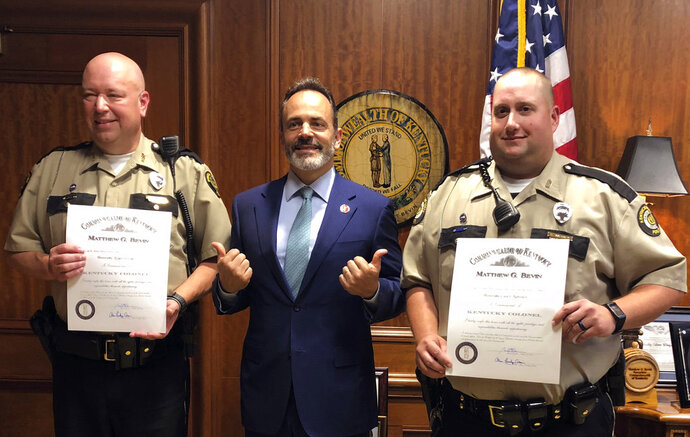 Gov. Matt Bevin, center, poses with Facilities Security Officers Roger Swiger, left, and Casey Mahoney, right, at the state Capitol in Frankfort, Ky., on Friday, Oct. 5, 2018. Bevin awarded both men an honorary commission of Kentucky Colonel for their part in saving the life of Kentucky NAACP President Raoul Cunningham. Cunningham collapsed during a meeting of the State Board of Election in September. Swiger and Mahoney administered CPR and a defibrillator until help arrived.  (AP Photo/Adam Beam)