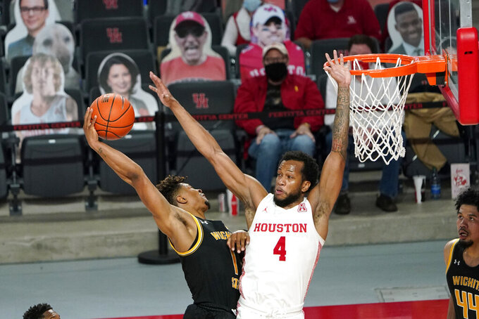 Wichita State's Tyson Etienne (1) goes up for a shot as Houston's Justin Gorham (4) defends during the second half of an NCAA college basketball game Wednesday, Jan. 6, 2021, in Houston. (AP Photo/David J. Phillip)
