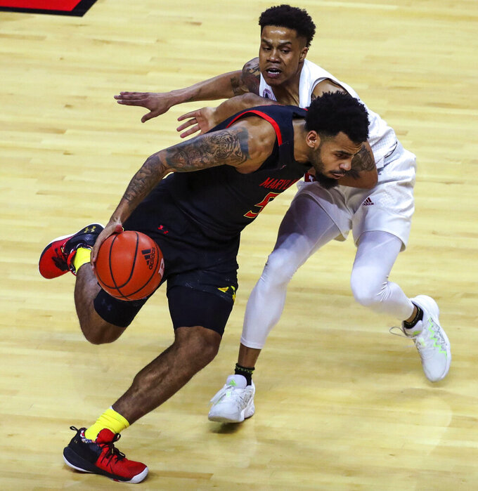 Maryland guard Eric Ayala (5) moves the ball as Rutgers guard Jacob Young (42) defends during the first half of an NCAA college basketball game in Piscataway, N.J., Sunday, Feb. 21, 2021. (Andrew Mills/NJ Advance Media via AP)