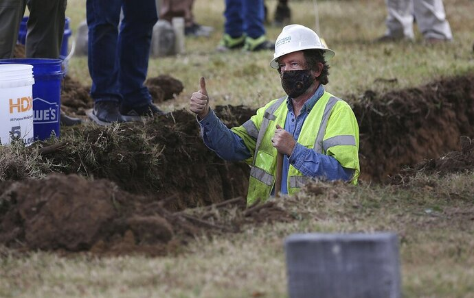 A researcher gives a thumbs-up as work continues on a second test excavation and core sampling in the search for remains at Oaklawn Cemetery from the 1921 Tulsa Race Massacre Wednesday, Oct. 21, 2020. (Mike Simons/Tulsa World via AP)