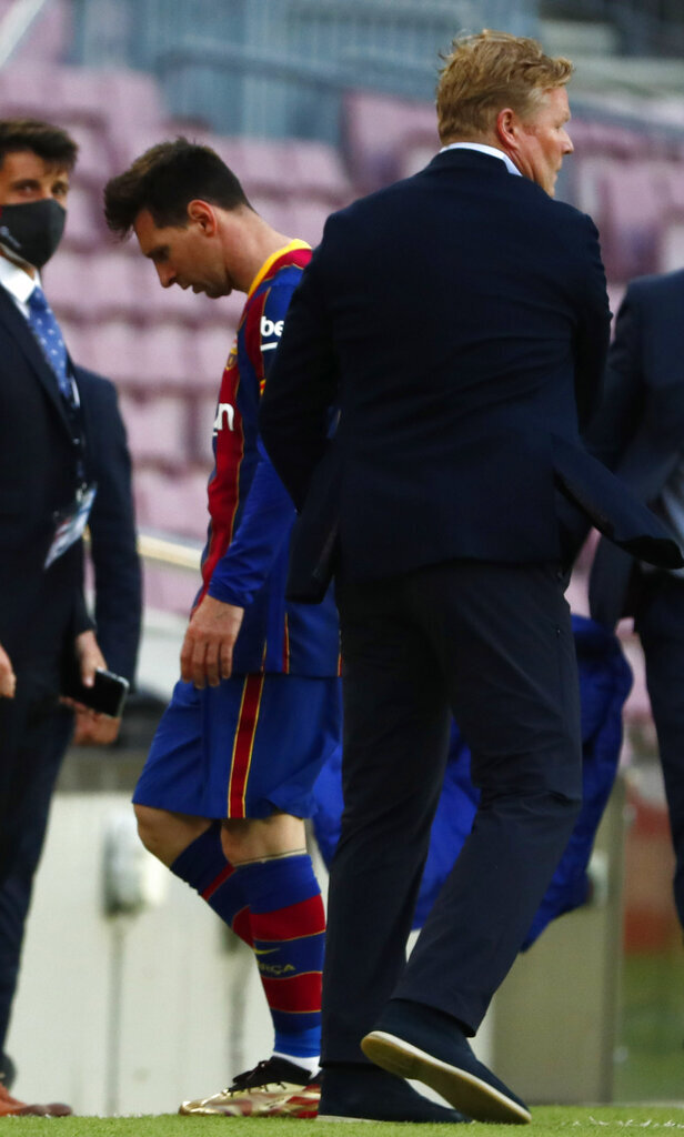 Barcelona's Lionel Messi walks past Barcelona's head coach Ronald Koeman at the end of the Spanish La Liga soccer match between FC Barcelona and Celta at the Camp Nou stadium in Barcelona, Spain, Sunday, May. 16, 2021. (AP Photo/Joan Monfort)