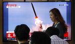 People watch a TV showing a file image of an unspecified North Korea's missile launch during a news program at the Seoul Railway Station in Seoul, South Korea, Tuesday, Sept. 10, 2019. North Korea launched at least two unidentified projectiles toward the sea on Tuesday, South Korea's military said, hours after the North offered to resume nuclear diplomacy with the United States but warned its dealings with Washington may end without new U.S. proposals. The sign reads