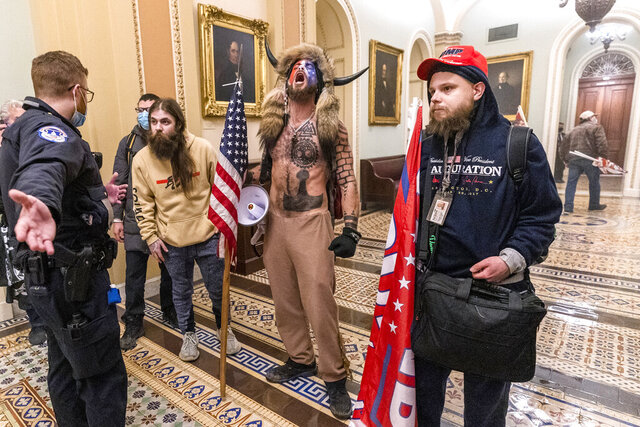 "FILE - In this Wednesday, Jan. 6, 2021 file photo, supporters of President Donald Trump, including Jacob Chansley, center with fur hat, are confronted by Capitol Police officers outside the Senate Chamber inside the Capitol in Washington. Chansley's lawyer says that he reached out White House Chief of Staff Mark Meadows about a possible pardon on behalf of the Arizona man, acknowledging it might be a reach but that ""there's nothing to lose."" (AP Photo/Manuel Balce Ceneta)"