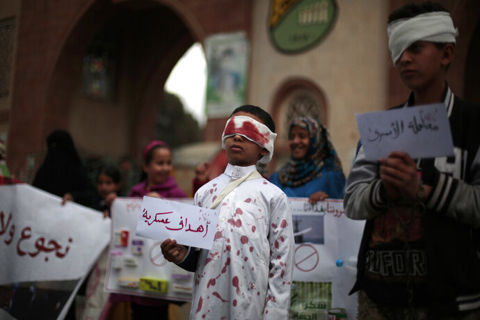 FILE -  In this now. 27, 2016, file, photo, a boy, center, with fake blood on his face and clothes to represent a victim, holds a poster with Arabic writing that reads,