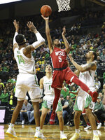 Washington State's Marvin Cannon, center, shoots between Oregon's Kenny Wooten, left, Will Richardson and Paul White, right, during the second half of an NCAA college basketball game Sunday, Jan 27, 2019, in Eugene, Ore. (AP Photo/Chris Pietsch)