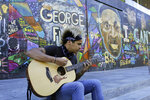 FILE - In this Aug. 27, 2020, file photo, Shane Braswell, who has protested at least 60 days since late May, spends an afternoon playing acoustic guitar in front of a huge mural in downtown Portland, Ore., that's dedicated to Black people killed by police.  Once hailed as one of the most livable cities in the U.S., Portland  is grappling with an uncertain future as it reaches a stunning benchmark: 100 consecutive nights of racial injustice protests marred by vandalism, chaos — and now, the killing of a supporter of President Donald Trump. (AP Photo/Gillian Flaccus, File)