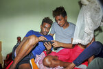 In this photo taken Thursday, Oct. 10, 2019, Eritrean under-20 soccer players Mewael Tesfai Yosief, left, and Simon Asmelash Mekonen look at a smartphone in a house where they are staying in Uganda. Four young players with Eritrea's national under-20 soccer team have defected during a tournament in Uganda, the latest players to leave one of the world's most tightly controlled regimes. (AP Photo)