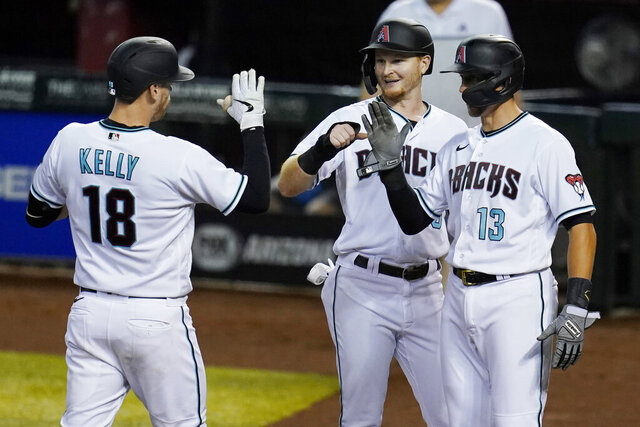 Arizona Diamondbacks' Carson Kelly (18) celebrates hit three-run home run against the Texas Rangers with Pavin Smith, middle, and Nick Ahmed (13) during the sixth inning of a baseball game Tuesday, Sept. 22, 2020, in Phoenix. (AP Photo/Ross D. Franklin)