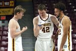 Minnesota players, from left, Brady Rudrud, Michael Hurt and Gabe Kalscheur look at a cellphone during NCAA college basketball media day Friday, Oct. 18, 2019, in Minneapolis. (AP Photo/Jim Mone)