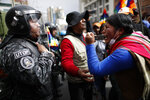 In this Tuesday, Nov. 12, 2019 photo, a supporter of Bolivia's former President Evo Morales yells at a police officer, telling him to respect the nation's indigenous people in La Paz, Bolivia. Former President Evo Morales, who transformed Bolivia as its first indigenous president, flew to exile in Mexico on Tuesday after weeks of violent protests, leaving behind a confused power vacuum in the Andean nation. (AP Photo/Natacha Pisarenko)