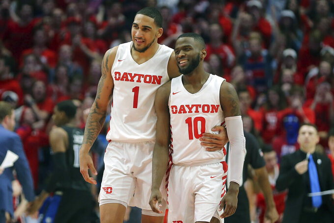 FILE - In this Feb. 1, 2020, file photo, Dayton's Obi Toppin (1) and Jalen Crutcher (10) are shown during the second half of an NCAA college basketball game against St. Louis in Dayton, Ohio. Dayton was third in The Associated Press college basketball poll, Wednesday, March 18, 2020, behind breakout stars Jalen Crutcher and Obi Toppin, the leading candidate for national player of the year. (AP Photo/Tony Tribble)