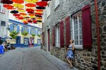 Paule Bergeron takes in the scene in Place-Royale in Old Quebec, Aug. 27, 2018. Quebec City offers compelling urban bike routes along the river, out to Montmorency Falls and through intriguing neighborhoods, as well as access to the Jacques-Cartier rail trail running through forest, farmland and meadows. (AP Photo/Cal Woodward)