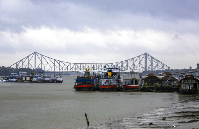 Mechanized boats used to ferry passengers are moored together to avoid losses under the inclement weather due to Cyclone Yaas in Kolkata, India, Wednesday, May 26, 2021. City heritage landmark Howrah Bridge is seen behind. Heavy rain and a high tide lashed parts of India's eastern coast as a cyclone pushed ashore Wednesday in an area where more than 1.1 million people have evacuated amid a devastating coronavirus surge. (AP Photo/Bikas Das)