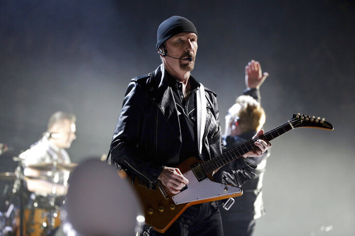 FILE - In this Sunday, Dec. 6, 2015, file photo, The Edge of U2 performs on stage during a concert, in Paris. A plan by U2 guitarist The Edge to build a cluster of mansions on a ridgeline above Malibu appears dead, after California's highest court declined to consider his last-ditch appeal. The musician, whose real name is David Evans, staged a 14-year legal fight to build five eco-friendly homes dubbed Leaves in the Wind in an undeveloped section of the Santa Monica Mountains west of Los Angeles. The state Supreme Court decided last week not to review a lower court ruling that denied approval to build on the land after the Sierra Club sued to block construction. (AP Photo/Thibault Camus, File)