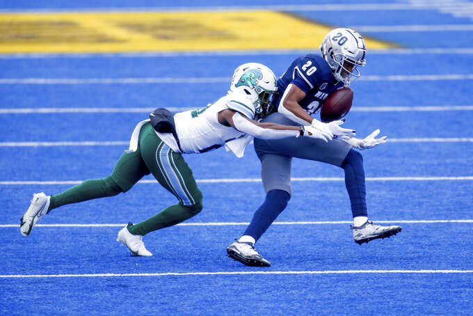 Nevada wide receiver Tory Horton (20) juggles the ball on catching as Tulane defensive back Ajani Kerr (21) moves in for the tackle during the first half of the Idaho Potato Bowl NCAA college football game, Tuesday, Dec. 22, 2020, in Boise, Idaho. (AP Photo/Steve Conner)