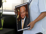 An employee holds a  portrait photo of the Director General of the International Atomic Energy Agency, IAEA, Yukiya Amano from Japan in Vienna, Austria, Monday, July 22, 2019. The IAEA announced the death of the agency's Director General Yukiya Amano at the age of 72 years. (AP Photo/Ronald Zak)