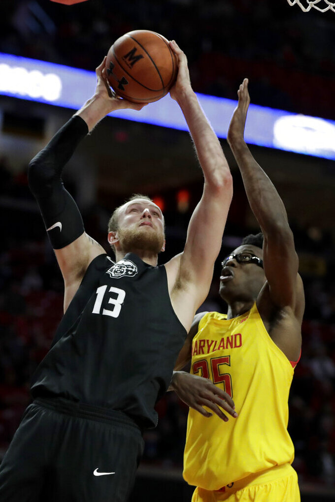 Oakland center Brad Brechting (13) goes up for a shot against Maryland forward Jalen Smith (25) during the first half of an NCAA college basketball game, Saturday, Nov. 16, 2019, in College Park, Md. (AP Photo/Julio Cortez)