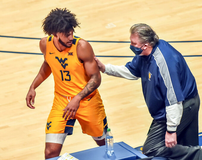 West Virginia head coach Bob Huggins, right, talks with Isaiah Cottrell (13) during the first half of an NCAA college basketball game against Iowa State in Morgantown, W.V., Friday, Dec. 18, 2020. (William Wotring/The Dominion-Post via AP)
