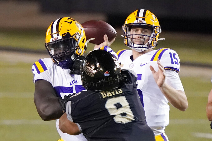 LSU quarterback Myles Brennan (15) passes as he is pressured by Vanderbilt defensive lineman Alex Williams (8) in the first half of an NCAA college football game Saturday, Oct. 3, 2020, in Nashville, Tenn. (AP Photo/Mark Humphrey)