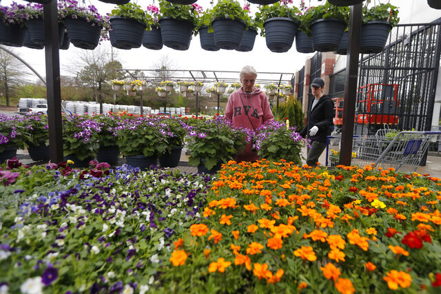 Gail Henrickson, left, and her daughter, Melissa, shop for plants at a local garden center as they stay at home during the coronavirus outbreak Monday March 23 , 2020, in Richmond, Va. The two work at a local restaurant that has closed down and are doing their spring gardening. (AP Photo/Steve Helber)