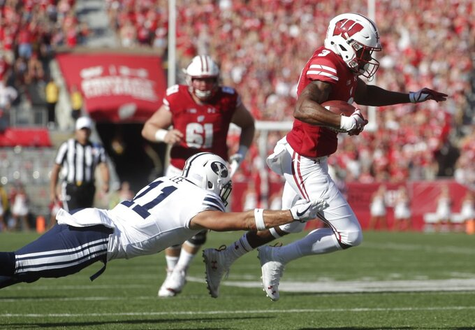 BYU's Austin Lee trips up Wisconsin's Kendric Pryor during the first half of an NCAA college football game Saturday, Sept. 15, 2018, in Madison, Wis. (AP Photo/Morry Gash)