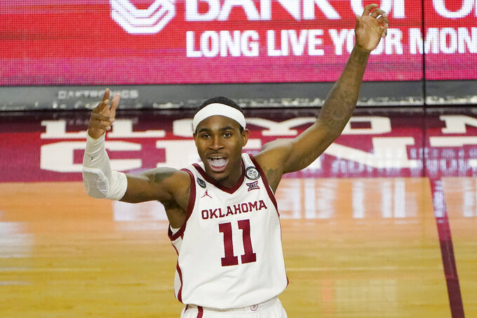 Oklahoma guard De'Vion Harmon (11) gestures to fans late in the second half of an NCAA college basketball game against West Virginia, Saturday, Jan. 2, 2021, in Norman, Okla. (AP Photo/Sue Ogrocki)