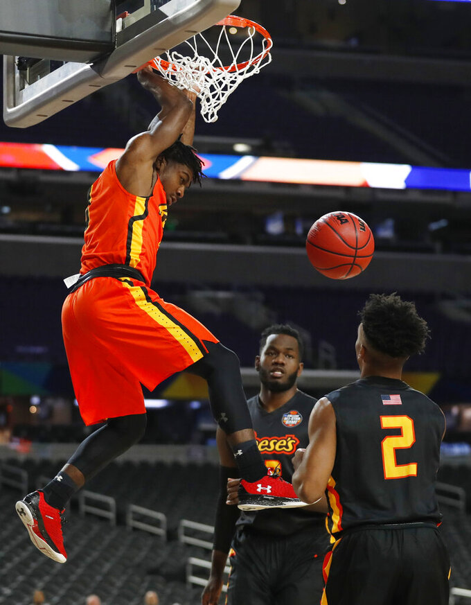 Campbell's Chris Clemons, left, dunks the ball over Cornell's Matt Morgan (2) during the College All-Star game at the Final Four NCAA college basketball tournament, Friday, April 5, 2019, in Minneapolis. (AP Photo/Jeff Roberson)