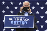Presidential candidate Joe Biden takes off his mask to speak during his drive-in rally at UAW Local 14 in Toledo, Ohio, on Monday, Oct. 12, 2020. (Lori King/The Blade via AP)