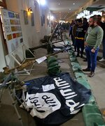 FILE - In this Feb. 1, 2019 file photo, a flag of the Islamic State group and some of the weapons they used in battle, are on display in the Popular Mobilization Forces War Museum in Baghdad, Iraq. U.S. and Iraqi officials say IS fighters facing defeat in Syria are slipping across the border into Iraq, where they are destabilizing the country's fragile security. Hundreds -- likely more than 1,000 -- IS fighters have crossed the open, desert border in the past six months. (AP Photo/Khalid Mohammed, File)
