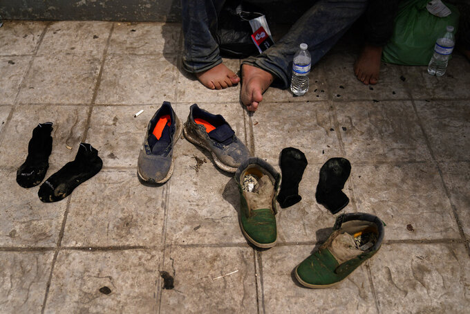 Two men from Honduras dry out their shoes after being returned from the U.S. to Mexico, Thursday, May 13, 2021, in Reynosa, Mexico. The Biden administration has agreed to let up to about 250 people a day in the United States at border crossings with Mexico to seek refuge, part of negotiations to settle a lawsuit over pandemic-related powers that deny migrants a right to apply for asylum, an attorney said Monday. (AP Photo/Gregory Bull)