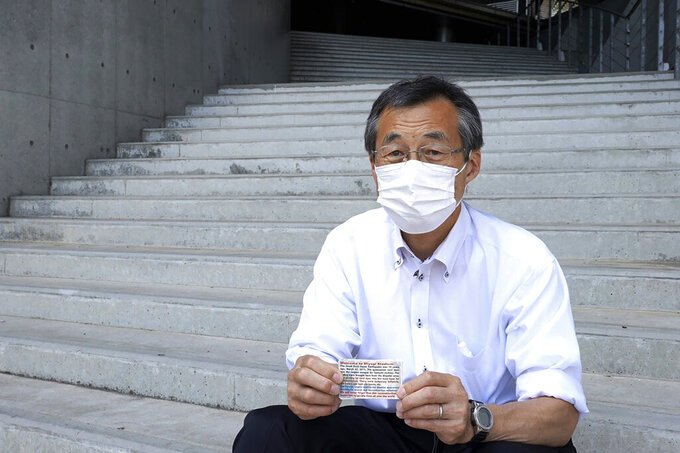 Olympic volunteer Atsushi Muramatsu shows business-card size flyers to express gratitude for support from overseas, during an interview with The Associated Press in Rifu, Japan, Thursday, July 29, 2021. He made the flyers to hand out to foreign media covering the 2020 Summer Olympics at Miyagi Stadium, where he is serving as a volunteer. (AP Photo/Chisato Tanaka)