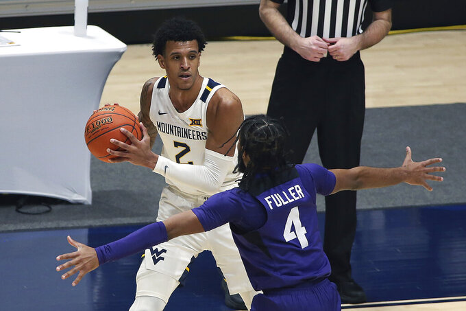 West Virginia forward Jalen Bridges (2) is defended by Texas Christian guard PJ Fuller (4) during the second half of an NCAA college basketball game Thursday, March 4, 2021, in Morgantown, W.Va. (AP Photo/Kathleen Batten)