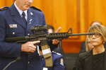 FILE - In this April 2, 2019, file photo, Police Sr. Sgt. Paddy Hannan shows New Zealand lawmakers an AR-15 style rifle similar to one of the weapons a gunman used to slaughter 50 people at two mosques, in Wellington, New Zealand. Dozens of Christchurch gun owners handed over their weapons in exchange for cash in the first of more than 250 planned buyback events around New Zealand after the government outlawed many types of semi-automatics. New Zealand lawmakers in April rushed through new legislation to ban so-called military-style weapons after a lone gunman killed 51 people at two Christchurch mosques in March. (AP Photo/Nick Perry, Fie)