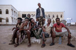 In this July 21, 2019 photo, Ethiopian migrants sit together and smoke, as they take shelter in the