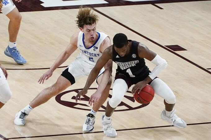 Mississippi State guard Iverson Molinar (1) tries to dribble past Kentucky guard Devin Askew (2) during the second half of an NCAA college basketball game in Starkville, Miss., Saturday, Jan. 2, 2021. (AP Photo/Rogelio V. Solis)