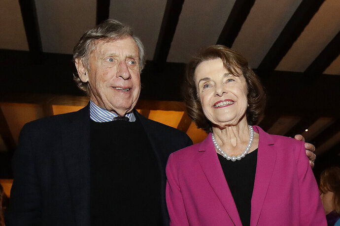 FILE - In this Nov. 6, 2018, file photo, U.S. Sen. Dianne Feinstein, right, smiles next to husband Richard Blum at an election night event in San Francisco. Sen. Feinstein's husband, University of California Regent Richard Blum, was named Thursday, Sept. 24, 2020, by the state auditor's office as one of the regents involved in admissions scandal where UC wrongly admitted dozens of wealthy, mostly white students as favors to well-connected people. (AP Photo/Jeff Chiu, File)