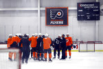 Philadelphia Flyers players gather with head coach Alain Vigneault, second from right, during training camp at the NHL hockey team's practice facility Monday, July 13, 2020, in Voorhees, N.J. (AP Photo/Matt Slocum)