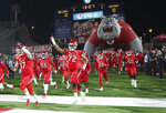 FILE - In this Nov. 23, 2019, file photo, Fresno State offensive lineman Dontae Bull, #72, heads into the stadium on senior night as they take on Nevada during the NCAA college football game in Fresno, Calif. This season, 39 major college football schools have scheduled 49 so-called buy games worth an estimated $65 million. If coronavirus disruptions cause Power Five teams to play more or only conference games, stretched athletic budgets could face huge holes. (AP Photo/Gary Kazanjian, File)