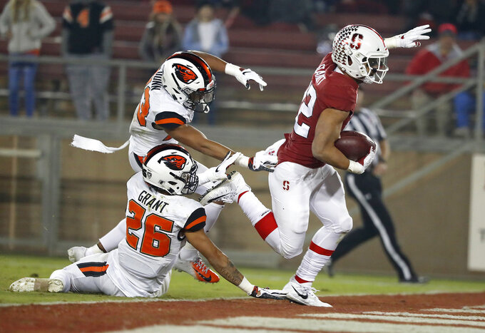 Stanford running back Cameron Scarlett (22) rushes for a touchdown past Oregon State cornerback Jaydon Grant (26) and cornerback Isaiah Dunn (23) in the second half during an NCAA college football game on Saturday, Nov. 10, 2018, in Stanford, Calif. (AP Photo/Tony Avelar)