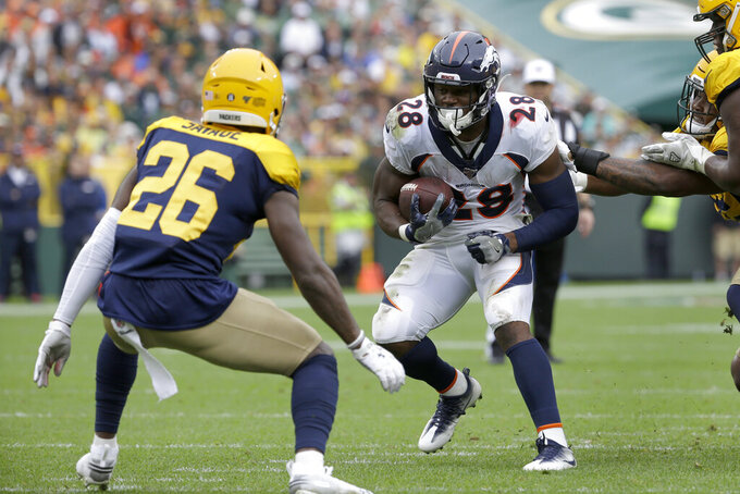 Denver Broncos running back Royce Freeman (28) runs with the ball as Green Bay Packers defensive back Darnell Savage (26) defends during the first half of an NFL football game Sunday, Sept. 22, 2019, in Green Bay, Wis. (AP Photo/Mike Roemer)