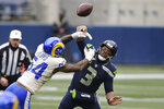 Los Angeles Rams outside linebacker Leonard Floyd (54) knocks the ball away as Seattle Seahawks quarterback Russell Wilson tries to pass during the first half of an NFL wild-card playoff football game, Saturday, Jan. 9, 2021, in Seattle. (AP Photo/Scott Eklund)