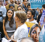 Alexandria Ocasio-Cortez, left, the surprise winner in the congressional race who unseated 20-year incumbent Joe Crowley in New York's Congressional District 14, listens to Zephyr Teachout, center, during a press conference, after endorsing her candidacy for Attorney General, Thursday, July 12, 2018, in New York. (AP Photo/Bebeto Matthews)