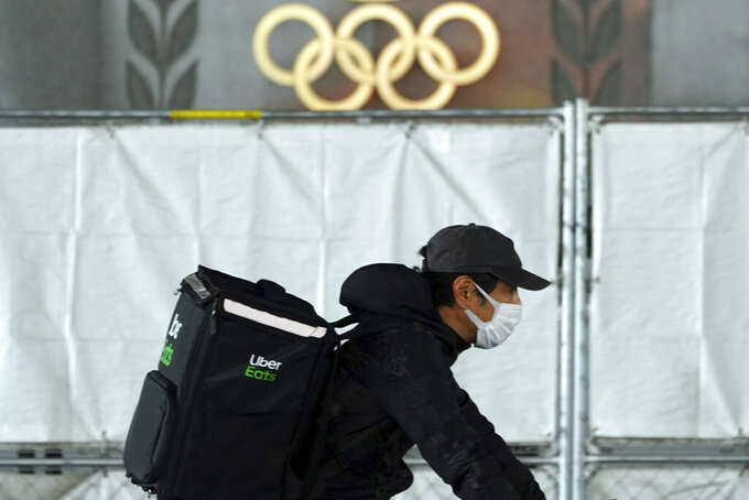 An Uber Eats delivery person carries items near the Japan National Stadium, where opening ceremony and other events are planned for postponed Tokyo 2020 Olympics, with engravings in honor of 1964 Tokyo Olympics seen on the side of the stadium wall behind the fence Tuesday, April 6, 2021, in Tokyo. Two top officials of Japan's ruling LDP party on Thursday, April 15, 2021, said radical changes could be coming to the Tokyo Olympics. One went as far to suggest they still could be canceled, and the other that even if they proceed, it might be without any fans.(AP Photo/Eugene Hoshiko)