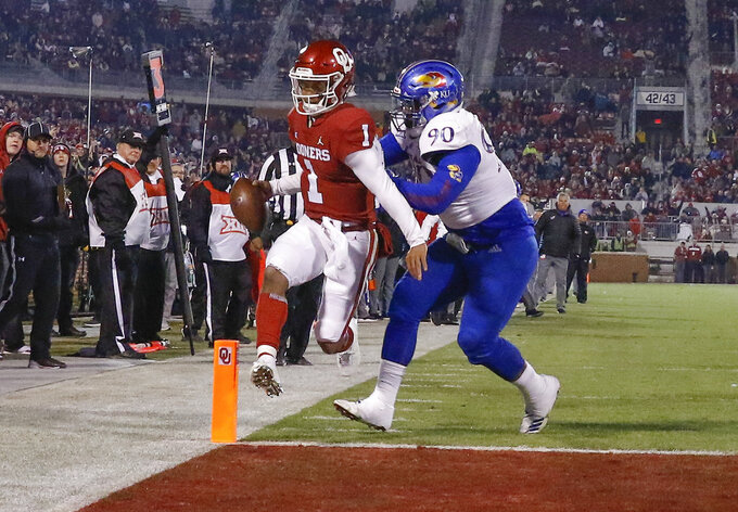 Oklahoma quarterback Kyler Murray (1) runs in for a touchdown ahead of Kansas defensive tackle Jelani Brown (90) during the second half of an NCAA college football game in Norman, Okla., Saturday, Nov. 17, 2018. Oklahoma won 55-40. (AP Photo/Alonzo Adams)