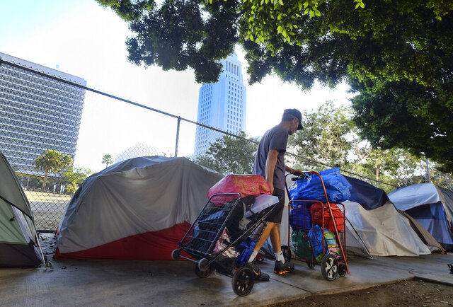 FILE - In this Monday, July 1, 2019, file photo, a homeless man moves his belongings from a street behind Los Angeles City Hall as crews prepared to clean the area. Over three days and nights this week, census takers are going to shelters, soup kitchens, mobile food van stops and other places across the U.S. where homeless people often gather. They will follow that with visits to encampments, under bridges, transit stations and other places where people live outside. (AP Photo/Richard Vogel, File)