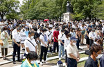 People offer silent prayer for the victims of U.S. atomic bombing at the time when the bomb was dropped, at the Atomic Bomb Hypocenter Park in Nagasaki, southern Japan, Sunday, Aug. 9, 2020. The Japanese city of Nagasaki on Sunday marked its 75th anniversary of the U.S. atomic bombing, with the mayor and dwindling survivors urging world leaders including their own to do more for a nuclear weapons ban. (Takuto Kaneko/Kyodo News via AP)